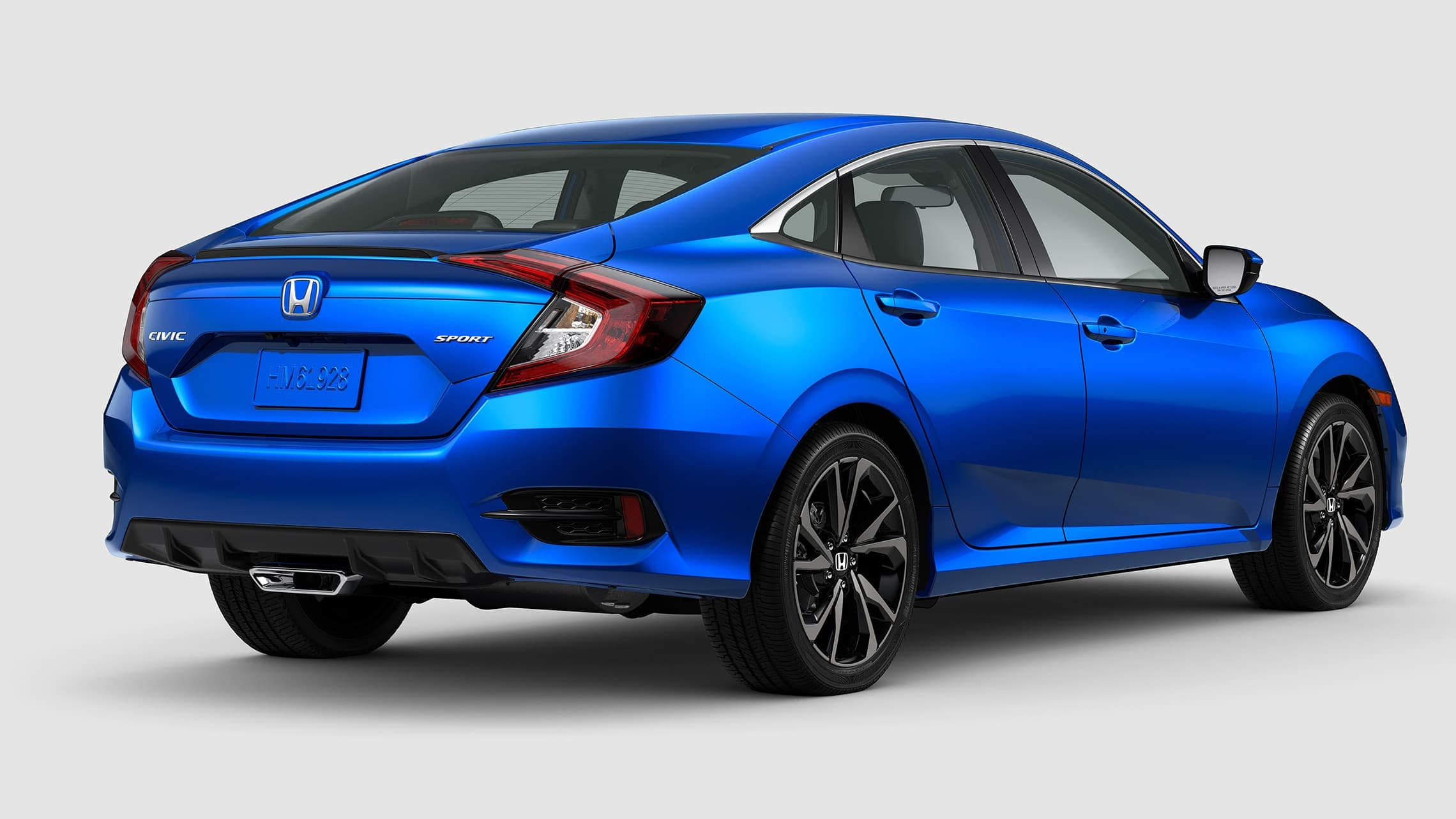 Rear passenger-side view of the 2020 Honda Civic Sport Sedan in Aegean Blue Metallic.
