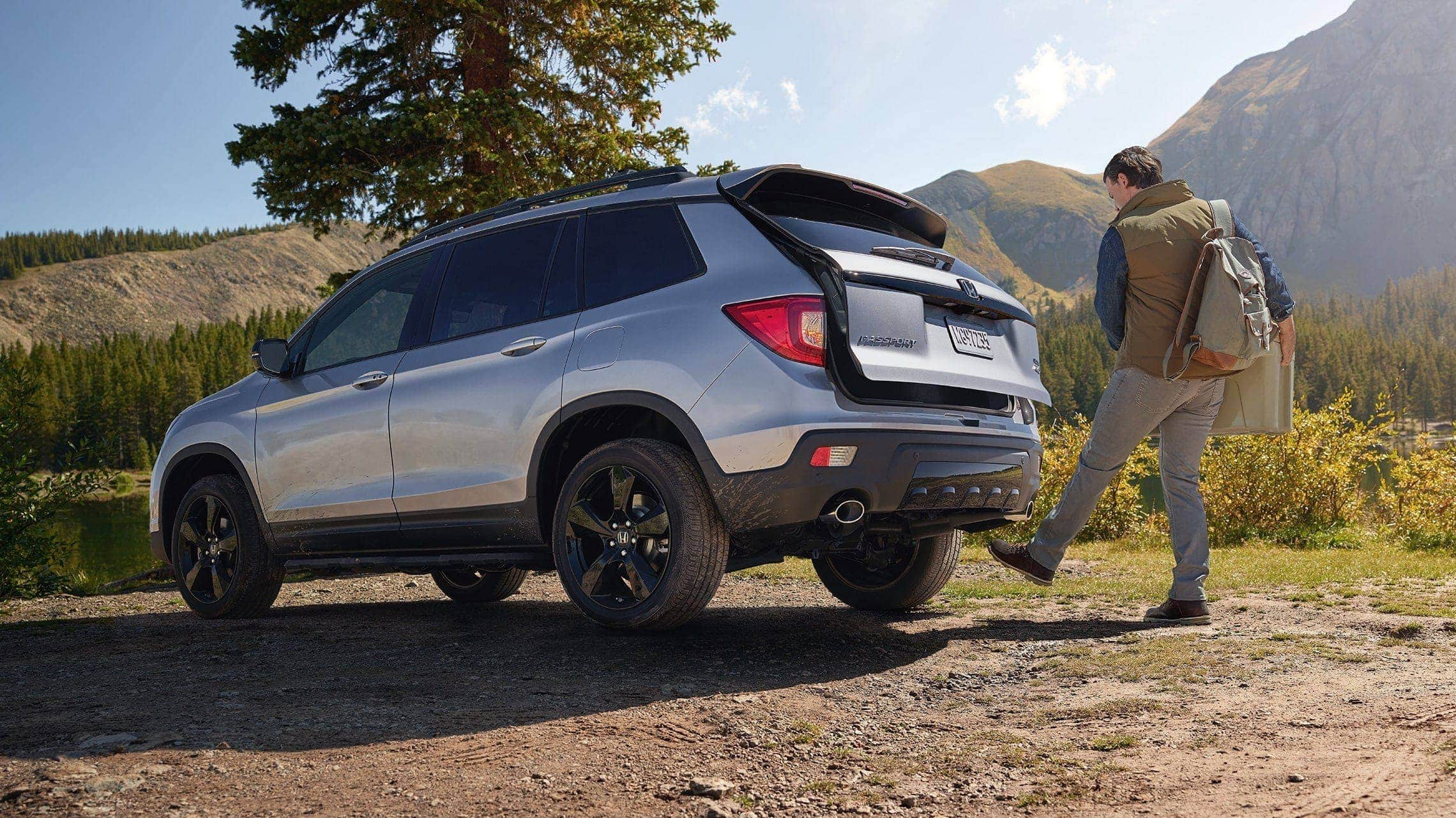 Driver-side rear 3/4 view of 2019 Honda Passport Elite in Lunar Silver Metallic, parked at campsite and demonstrating the hands-free access power tailgate feature.