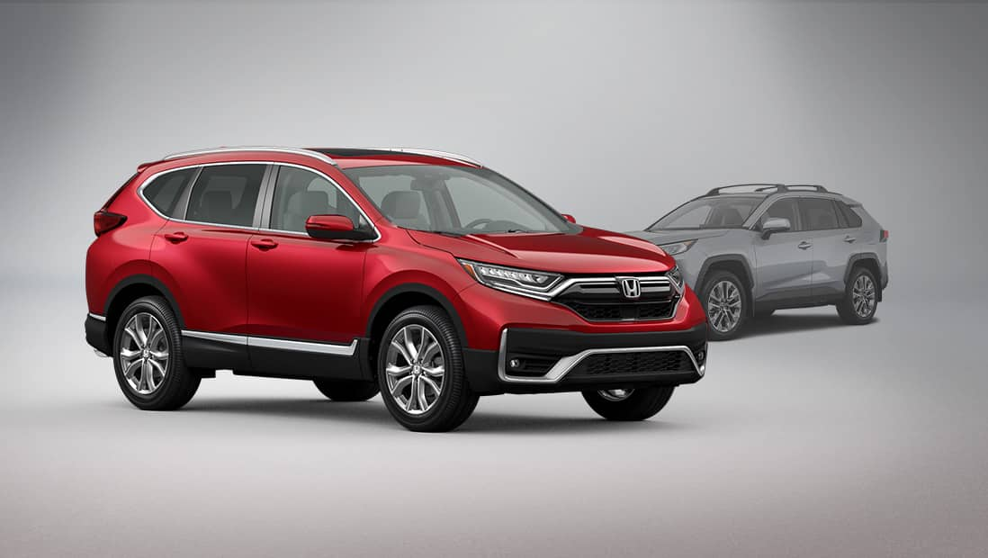 Front passenger-side view of the 2020 Honda CR-V Touring, in Deep Scarlet Pearl, parked in studio environment next to a Toyota RAV4.