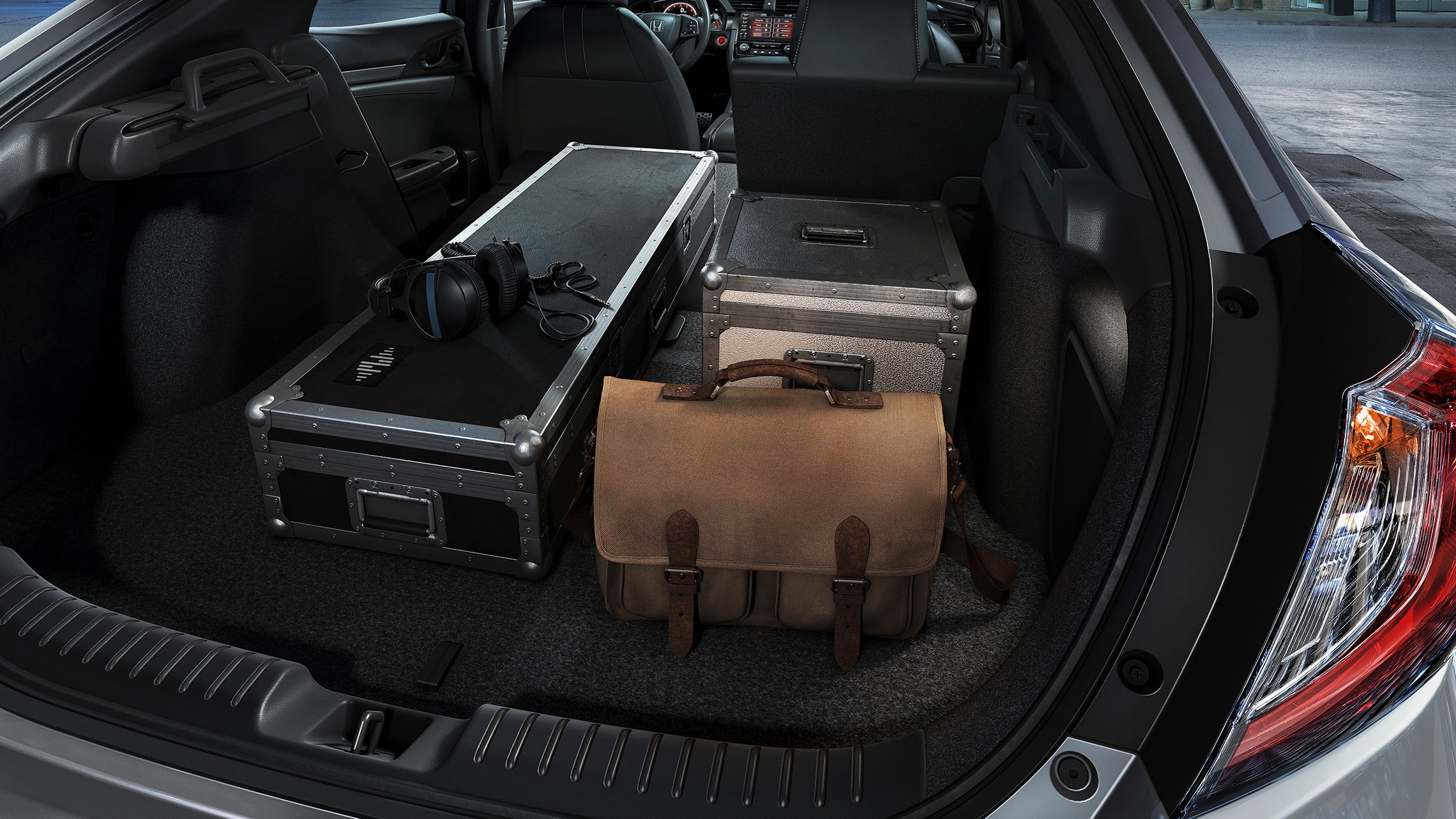 Various items loaded into cargo space of the 2021 Honda Civic Sport Touring Hatchback with 60/40 split fold-down rear seatback.