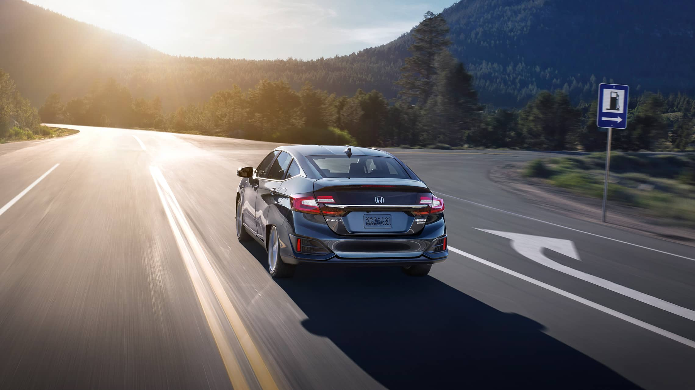 Rear of 2020 Clarity Plug-In Hybrid in Modern Steel Metallic driving along tree-lined road.