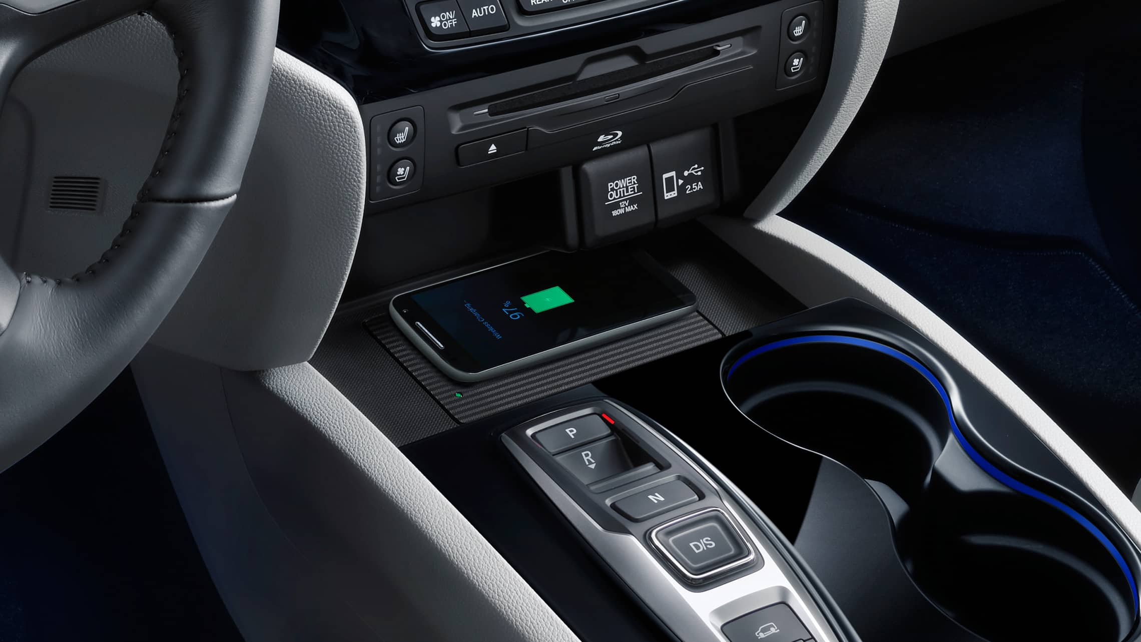 Interior cabin close-up view of wireless phone charging detail in 2021 Honda Pilot Elite with Gray Leather.