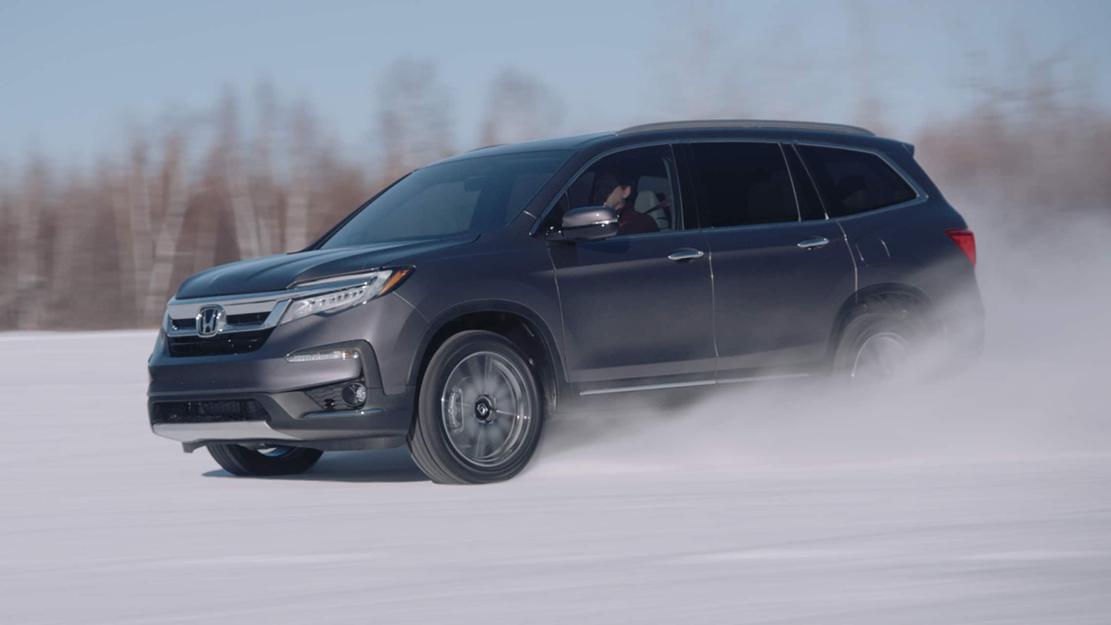 View of 2020 Honda Pilot Elite demonstrating capability with a snowy road environment.
